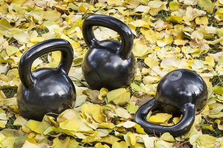 three heavy iron  kettlebells outdoors in a fall scenery  - outdoor fitness concept photo