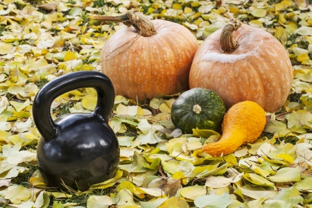 heavy iron  kettlebell outdoors in a fall scenery  with pumpkin and squash - outdoor fitness concept