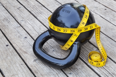 kettlebell and measuring tape on wooden deck - fitness and exercise concept photo