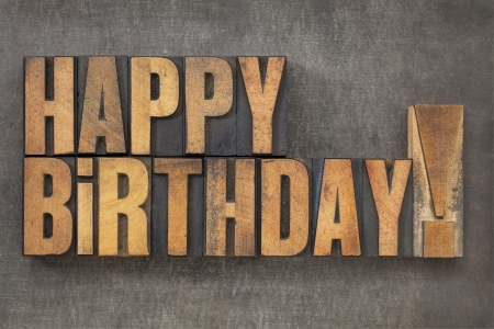 letterpress words: Happy Birthday  -  text in vintage letterpress wood type blocks on a grunge metal background