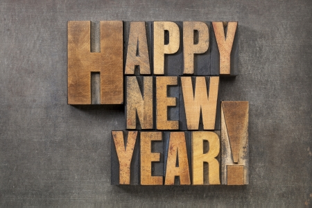letterpress words: Happy New Year  - text in vintage letterpress wood type blocks on a grunge metal background Stock Photo