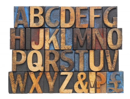 English alphabet with punctuation symbols  in vintage letterpress wood type blocks stained by blue, red and black ink, isolated on white photo