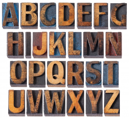 prinitng block: complete English alphabet - collage of 26 isolated vintage wood letterpress printing blocks, scratched and stained by blue, red and black ink Stock Photo