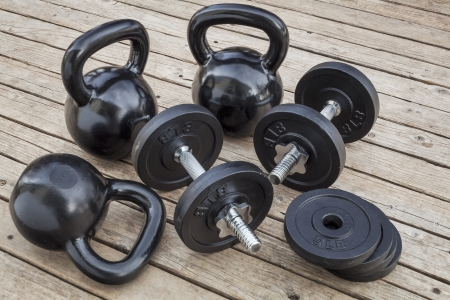 exercise weights - kettlebells and dumbbells on a wooden deck - a home gym concept Stock Photo