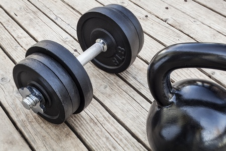 exercise weights - kettlebell and dumbbells on a wooden deck - a home gym concept Stock Photo - 16529552