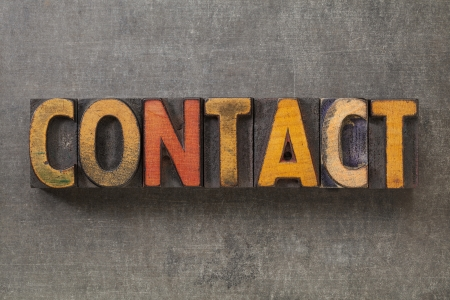 contact word in vintage letterpress wood type blocks against grunge metal background Stock Photo - 16604445