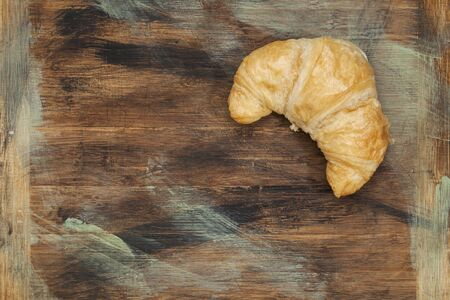 croissant roll on a grunge painted wood board