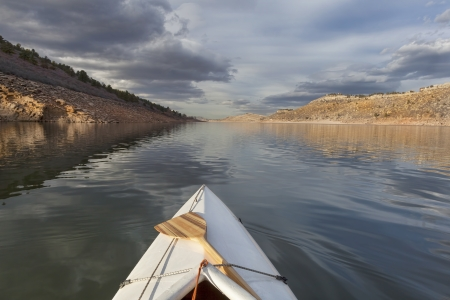horsetooth reservoir: expedition decked canoe and wooden paddle on a narrow mountain lake - Horsetooth Reservoir near Fort Collins, Colorado, late fall scenery
