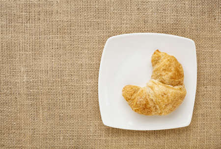 croissant roll on a white china plate against burlap canvas board Stock Photo - 16770329
