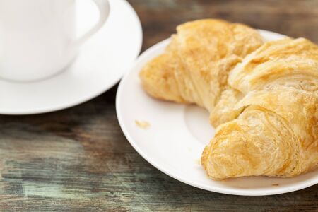 croissant roll with espresso coffee cup on grunge painted wooden table, shallow depth of field Stock Photo - 16770337