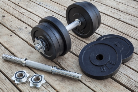cast iron dumbbell and weight plates on wooden deck - home gym concept Stock Photo - 16770341