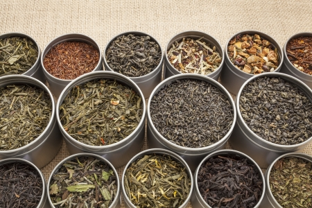 herb tea: samples of loose leaf green, white, black red, and herbal tea in metal cans on canvas background Stock Photo