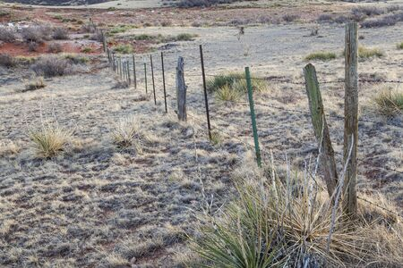 cattle barbed wire fence in semi desert ranch in northern Colorado near Wyoming border photo