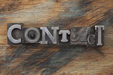 printing block block: contact word in vintage metal letterpress  type on a grunge painted wood background
