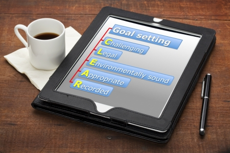 CLEAR  challenging, legal, environmentally sound, appropriate, recorded  goal setting concept - a diagram on a tablet computer with stylus pen and espresso coffee cup against grunge wooden table