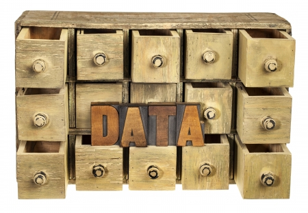data storage concept - data word in vintage letterpress wood type and primitive rustic wooden apothecary or catalog drawer cabinet photo