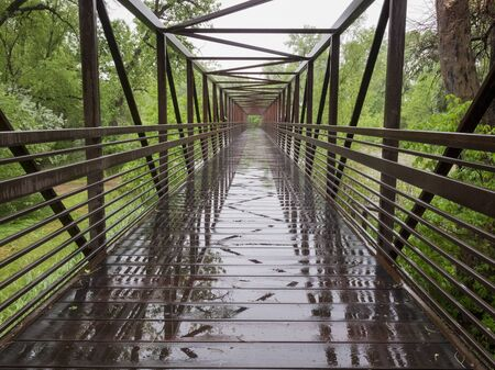 wet bike trail bridge over a flooding river, springtime Stock Photo - 17018037