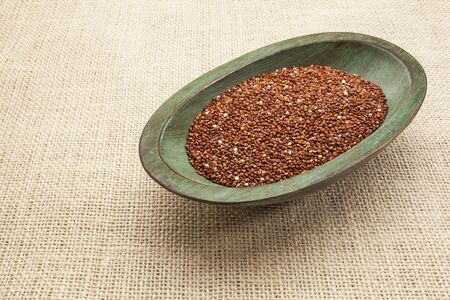 red quinoa grain in a rustic wood bowl against burlap canvas Stock Photo - 17067701