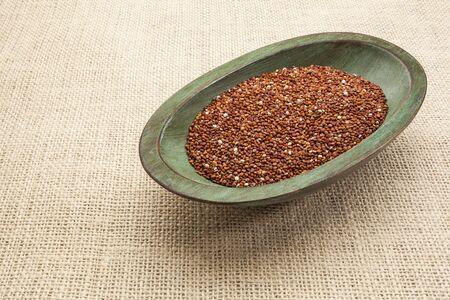red quinoa: red quinoa grain in a rustic wood bowl against burlap canvas Stock Photo