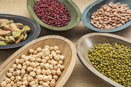 ingedient: variety of legumes (fava bean, mung bean, adzuki, pinto, chickpea) in colorful rustic wood bowls on canvas Stock Photo