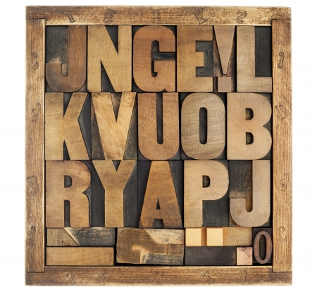 random letters of alphabet and punctuation symbols - vintage letterpress wood type blocks in rustic box isolated on white photo