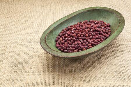 Japanese adzuki (aduki, azuki) beans in a rustic wood bowl against burlap canvas Stock Photo - 17113356