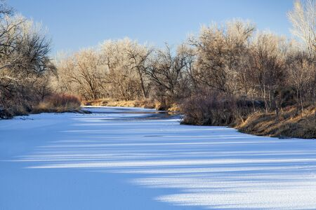 poudre river: frozen Cache la Poudre River in Fort Collins, Colorado with shadow patterns on ice