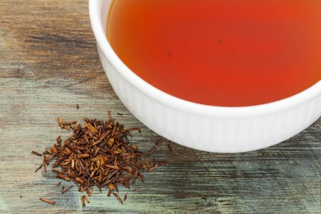 caffeine free: rooibos red tea  - a white cup of drink and loose leaves on wood background, tea made from the South African red bush, naturally caffeine free