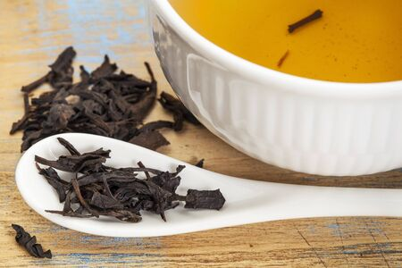 Se Chung Oolong tea - a white cup of drink and loose leaves on teaspoon Stock fotó