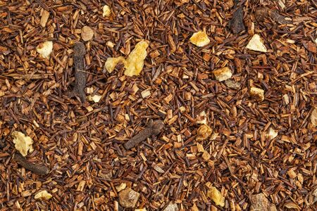rooibos tea: background texture of rooibos tea with cinnamon, orange peels, and clove Stock Photo