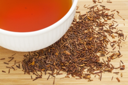 caffeine free: rooibos red tea  -  a white cup of drink and loose leaves on bamboo wood background, tea made from the South African red bush, naturally caffeine free Stock Photo
