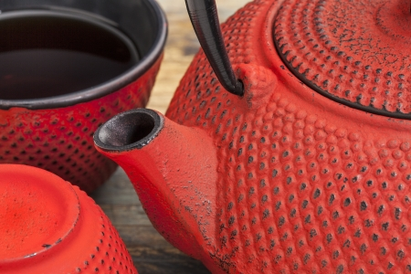 japenese: red tetsubin with a cup of tea - a detail of a traditional cast iron Japenese teapot