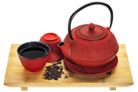 red hobnail tetsubin (traditional cast iron Japenese teapot) with a cup of oolong tea on a bamboo tray Banco de Imagens