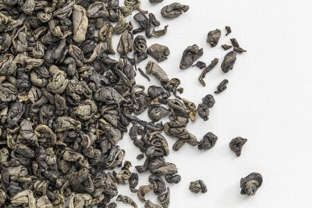 background texture of loose leaf Chinese gunpowder (pearl) green tea spilled over white artist canvas Stock Photo - 17305806