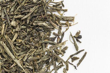 loose leaf: textura de fondo de hojas sueltas de t� verde Sencha derram� sobre lienzo artista blanco Foto de archivo