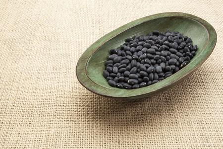 turtle bean: black turtle beans in a rustic wood bowl against burlap canvas