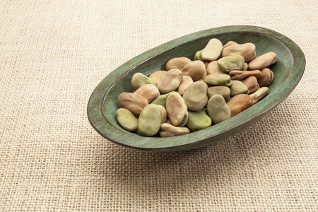 fava (broad) beans  in a rustic wood bowl against burlap canvas Stock Photo - 17305841