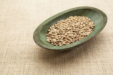 green lentils in a rustic wood bowl against burlap canvas Stock Photo - 17305848
