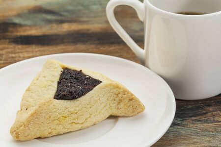 hamantasch: fruit hamantaschen cookie  on a plate with a cup of coffee - a traditional pastry in Ashkenazi Jewish cuisine for holiday of Purim