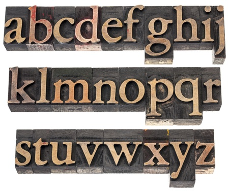 english letters: wood type alphabet in letterpress printing blocks stained by color inks, three rows isolated on white