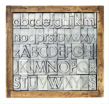 letterpress  type: lowercase and uppercase English alphabet - vintage metal letterpress type blocks in a wooden box,  isolated on white