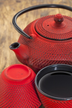 hobnail: red hobnail tetsubin with a cup of tea - a detail of a traditional cast iron Japanese teapot set