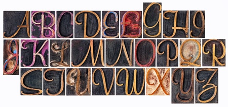 prinitng block: complete English alphabet  in ornamental script wood type - a  collage of 26 isolated letterpress printing blocks stained by color and black ink Stock Photo
