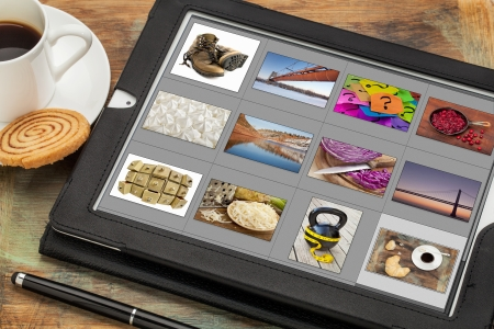 image editing: reviewing image library (grid of thumbnails) on a digital tablet computer, table with a cup of coffee; all displayed pictures copyright by the photographer