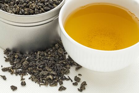 gunpowder: gunpowder green tea - a white cup of drink and loose leaves on canvas Stock Photo