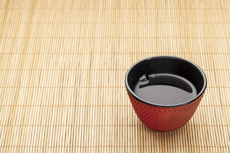 Japanese cup of tea on a bamboo mat - a traditional cast iron red hobnail design with black enamel inside Stock Photo - 17530229