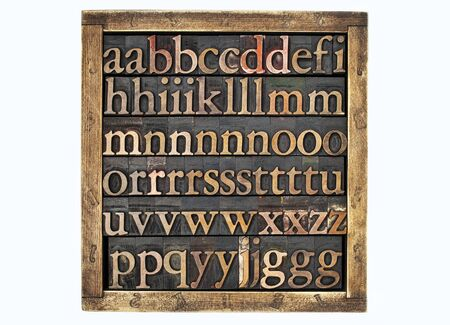 wooden box of vintage letterpress alphabet printing blocks stained by color inks Stock Photo - 17530199