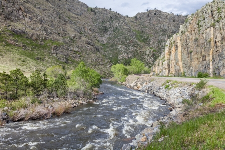 Cache la Poudre RIver and highway in canyon west of Fort Collins, Colorado, springtime flow 版權商用圖片