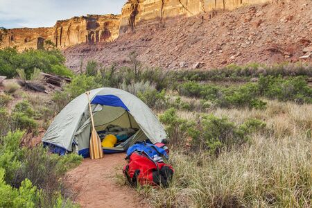 canoe paddle: sunrise over river camping in Canyonlands National Park- a tent with canoe paddle and waterproof bags on the shore of Green River