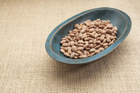 pinto bean: pinto (speckled) bean in a rustic wood bowl against burlap canvas